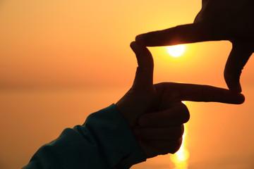 hands make heartshape against sunset seaside