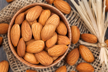 Almonds super foods in a wooden dish on vintage textile backgrou