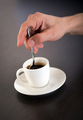 Hand Stirring Cup of Espresso Coffee with Spoon
