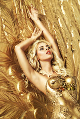 Blond sensual lady lying on the gold wings