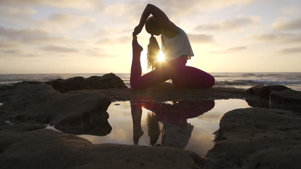 Woman Practicing Advanced Yoga Pose At Sunset With Lens Flare