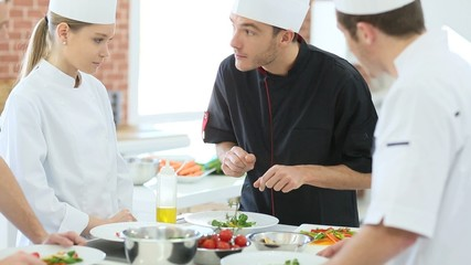 Chef teaching students how to prepare dish