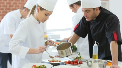 Chef checking on student preparing dish