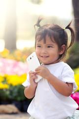 Cute little girl holding smart phone in flower garden