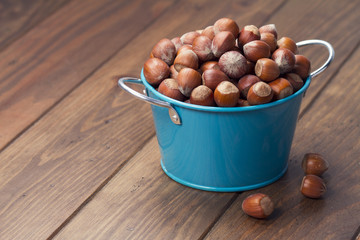Hazelnuts in a blue bucket on a wooden table. Vintage Style.