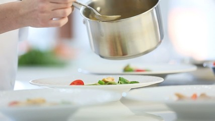 Closeup of woman in restaurant kitchen pouring sauce