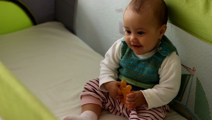 Cute baby girl sitting in bed