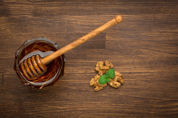 Bowl of honey nuts and mint on wooden table. Symbol of healthy