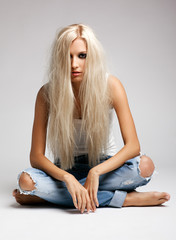 Blonde woman in ragged jeans and vest