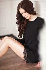 Young brunette lady in black lacy dress posing in white room.