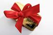 Leinwandbild Motiv Goldbarren  mit roter Geschenkschleife