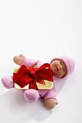 Goldbarren  mit roter Geschenkschleife auf Baby Puppe