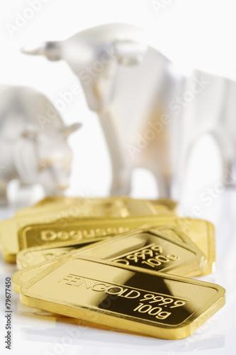 Goldbarren vor Bulle und Bär, Börse, Symbolbild - 79677450