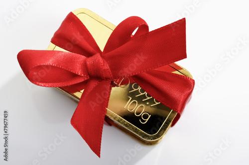 Goldbarren  mit roter Geschenkschleife - 79677459