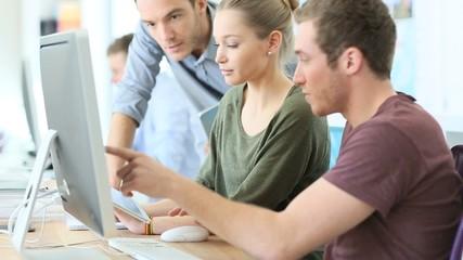 Teacher helping students in digital design