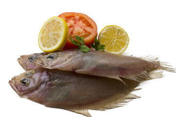 fresh fish isolated with tomato and lemon