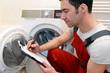 Leinwanddruck Bild - Techniker repariert Waschmaschine