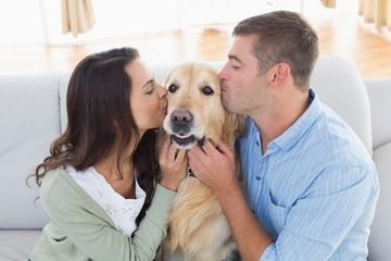 Couple kissing Golden Retriever on sofa