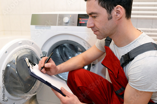 Leinwanddruck Bild Techniker repariert Waschmaschine