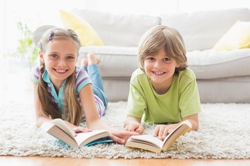 Happy siblings holding books while lying on rug