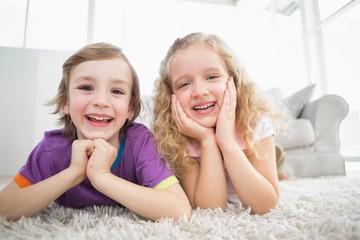 Happy siblings lying on rug at home