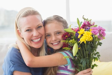 Mother with bouquet embracing daughter in house
