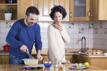 Man whisking dough and woman eating homemade cupcakes