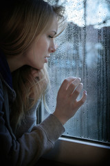 woman looking through window with raindrops