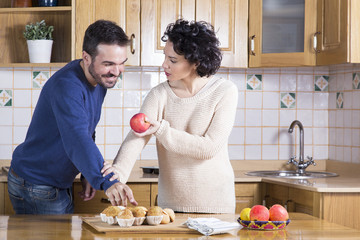 Man taking delicious cupcake while her woman offering him apple