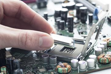 Technician inserting CPU in motherboard