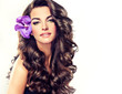 Beautiful girl with long curly brown hair , flower in hair