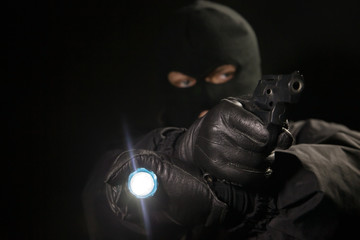 Robber with a gun and a flashlight in his hand