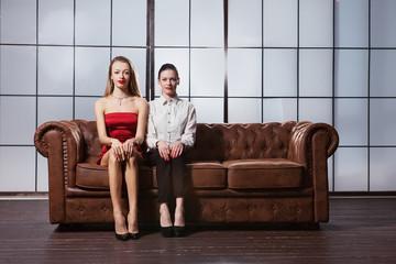 Beautiful girls are sitting on the sofa.