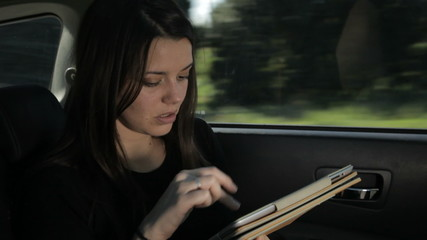 business woman working on ipad while sitting in back of the car