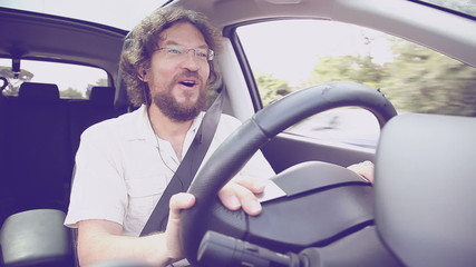 Man on the phone while driving car laughing