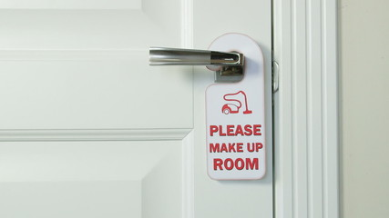 Guest hanging make up room sign on the door of hotel room