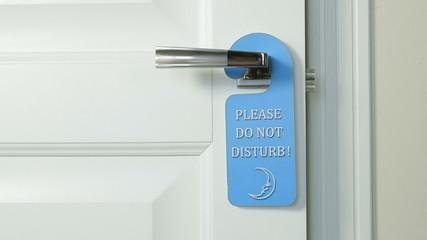 Blue hanger Please Do Not Disturb on the door of hotel room