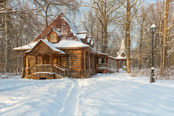 Wooden house in the old style in a snowy forest