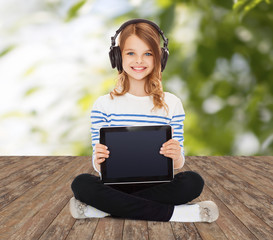 happy girl with headphones showing tablet pc