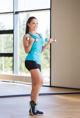 smiling woman exercising with dumbbells in gym