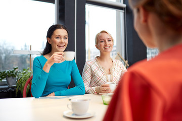 happy young women drinking tea or coffee at cafe