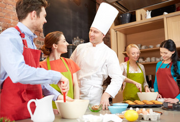 happy friends and chef cook baking in kitchen
