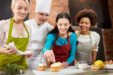 happy women and chef cook baking in kitchen