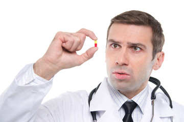 Close up of a scared medical doctor looking at yellow-red pill \