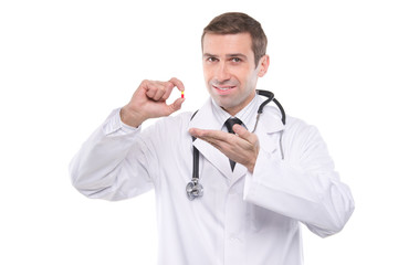 Smiling medical doctor with yellow-red pill \ Isolated on white