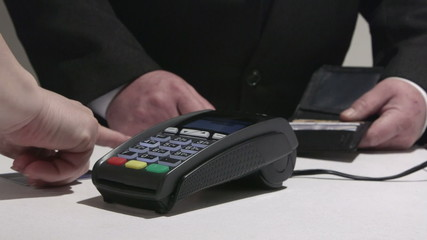 Consumer using credit card processing terminal entering PIN code