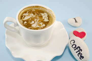 White cup of coffee with decorated foam