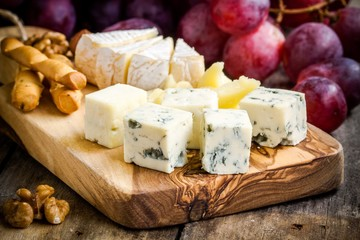 Emmental, Camembert, Parmesan, blue cheese closeup, with grapes