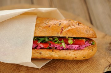 Sandwich with beetroot, bell pepper and scallion wrapped in pape