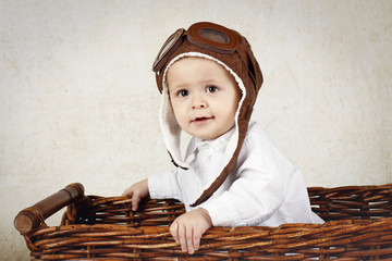 Funny little pilot in wicker basket